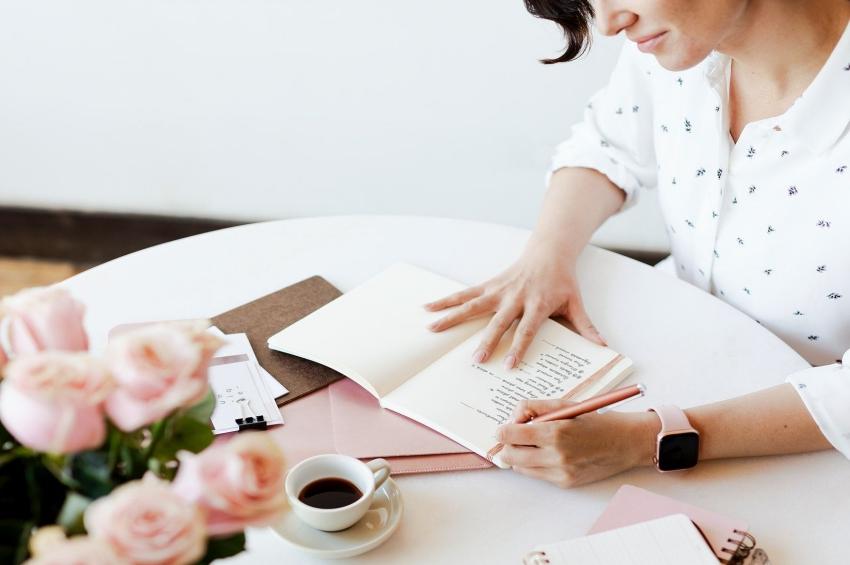 femme qui ecrit dans un carnet avec un cafe et des fleurs