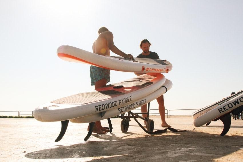 hommes sur la plage avec planche de paddle