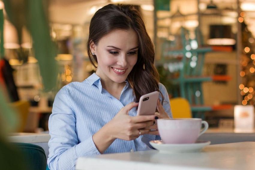 jeune femme assise a un terrasse avec un cafe sur son telephone